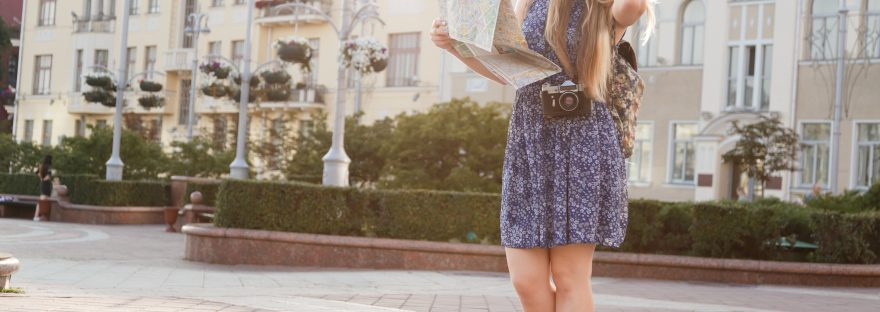 Woman with backpack and camera holds city map as tourist