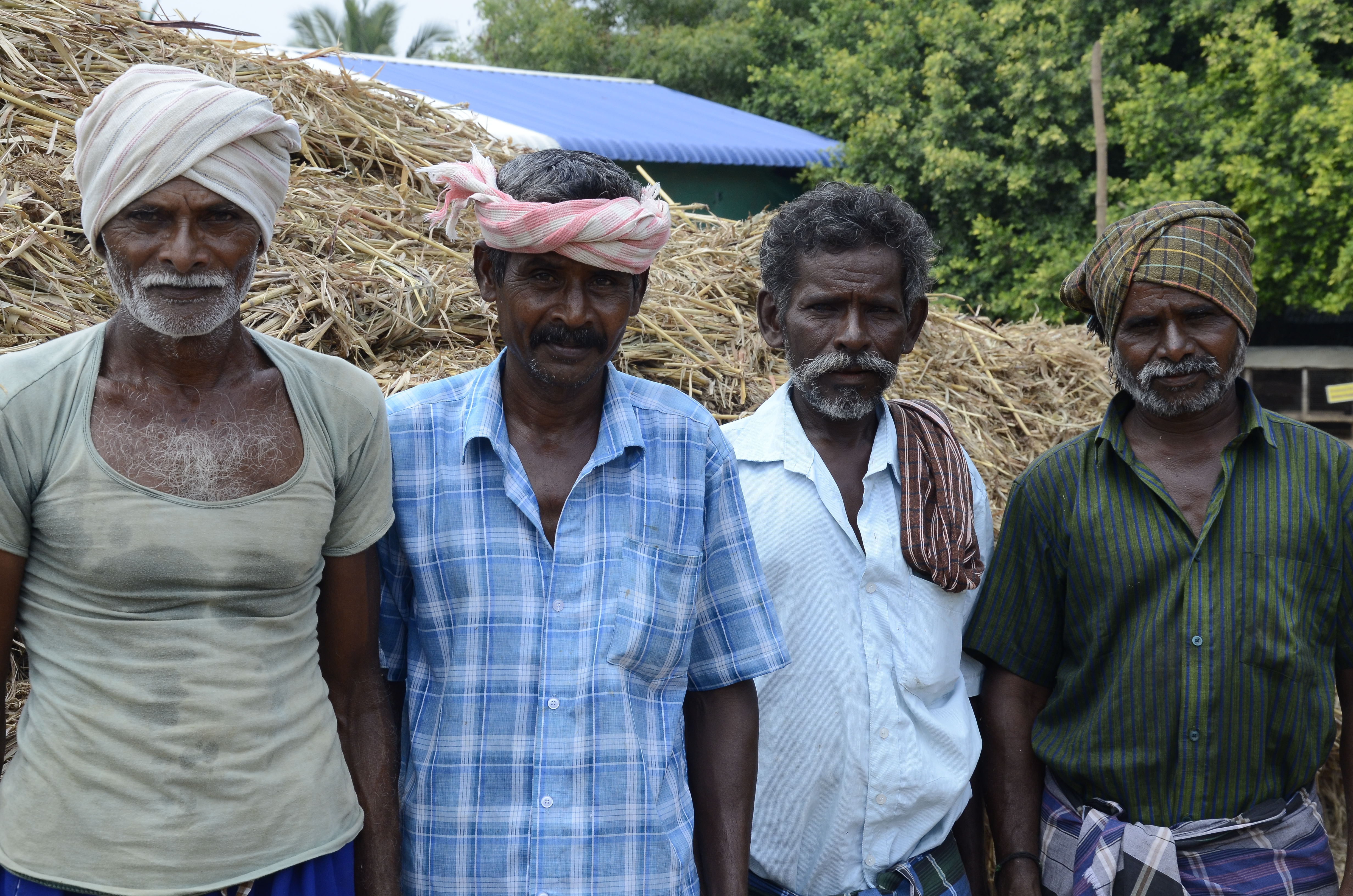 four working indian men posing for a picture