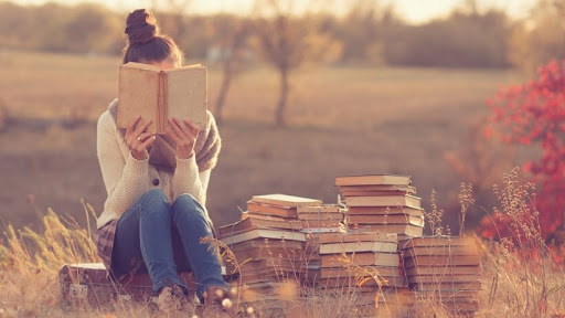 girl sitting alone in a field reading books