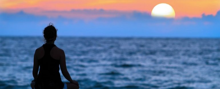 woman sitting on the beach at sunset meditating