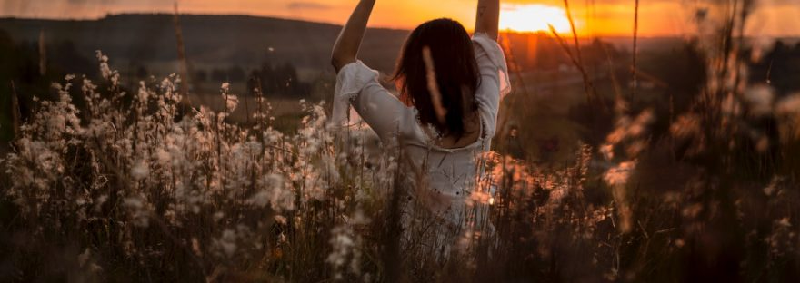 girl standing in a field at sunset