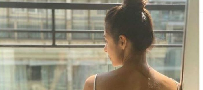 girl with hair in a bun looking out the window