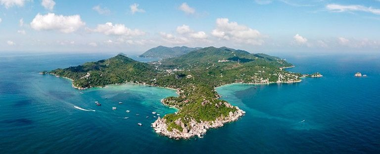 the island of koh tao as seen from the air, an island surrounded by blue ocean
